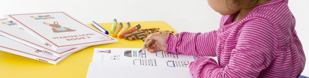 A child completing an activity page, with crayons on the table
